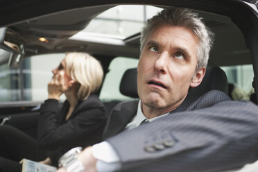 Germany, Hamburg, Two Business people sitting in car, Businessman looking up, portrait, close-up - WESTF13874