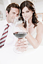 Couple in restaurant, man holding glass of red wine, portrait - WESTF13830