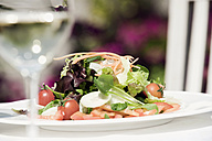 Italy, South Tyrol, Mixed salad on plate with a glass of white wine - WESTF13782