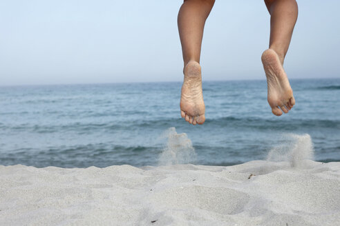 Italy, Sardinia, Feet of Jumping Person, low section - MBEF00019