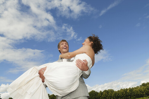 Germany, Bavaria, Groom lifting bride, laughing, portrait - NHF01137