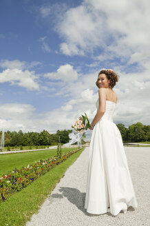 Germany, Bavaria, Bride in park holding bunch of flowers, smiling, portrait - NHF01128