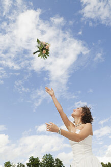 Germany, Bavaria, Young bride throwing a bouquet into the sky - NHF01125