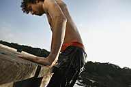 Germany, Berlin, Young man climbing on jetty, side view - VVF00091