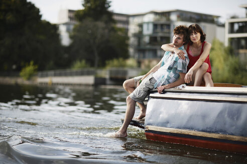 Germany, Berlin, Young couple sitting on motor boat, portrait - VVF00067
