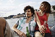 Germany, Berlin, Young couple on motor boat, holding bottles, portrait, close-up - VVF00064