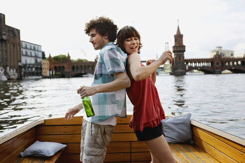 Germany, Berlin, Young couple on motorboat, holding bottles, standing back to back - VVF00052