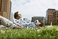 Germany, Berlin, Young couple lying in meadow, high rise buildings in background - VVF00031