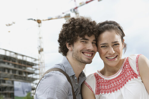 Germany, Berlin, Young couple in front of new building, cranes in background - VVF00022