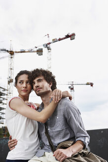 Germany, Berlin, Young couple in front of new building, cranes in background - VVF00016