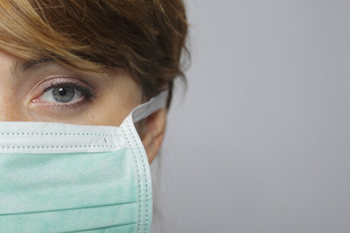 Female doctor wearing surgical mask, portrait, close-up - MBEF00022