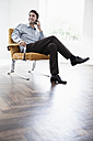Businessman sitting in chair, using mobile phone - JRF00169