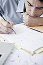 Businessman in office writing, portrait - JRF00157