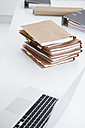 Stack of files, laptop and folders in conference room - JRF00145
