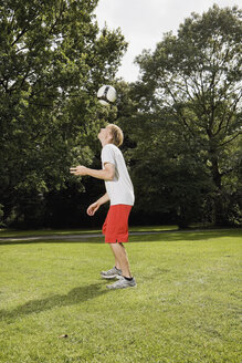Germany, Berlin, Young man on lawn playing with soccer ball - SKF00130