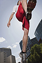 Germany, Berlin, Young man jumping in air, low angle view - SKF00109