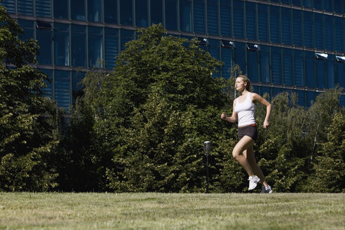 Germany, Berlin, Young woman jogging - SKF00073