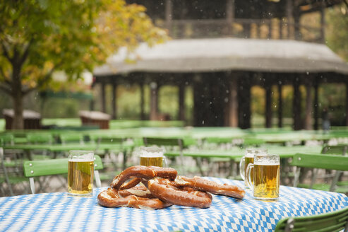 Germany, Bavaria, English Garden, Beer mugs and pretzel on table, chinese tower in background - WESTF14085