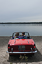 Germany, Berlin, Lake Wannsee, Young couple in cabriolet embracing, side view, portrait - WESTF13986