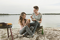Germany, Berlin, Lake Wannsee, Young couple having a barbecue - WESTF13977