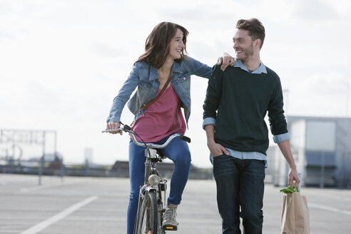 Germany, Berlin, Young couple with bicycle and paper bag - WESTF13953