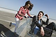 Germany, Berlin, Young woman pushing young man in shopping cart - WESTF13935