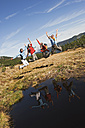 Austria, Salzburger Land, Four hikers by lake jumping in air - HHF03114