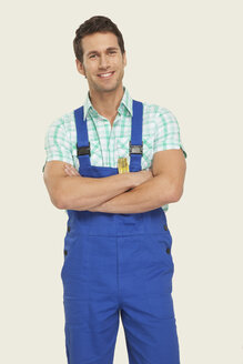 Man wearing overall smiling, arms crossed, portrait - WESTF14474