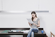 Woman sitting on desk reading document. - WESTF14444