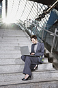 Germany, Bavaria, Munich, Business woman at subway station using laptop, sitting on staircase - WESTF14132