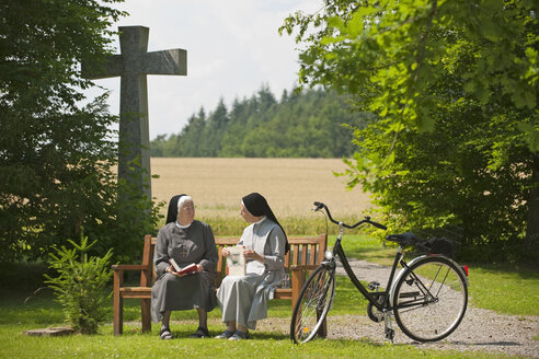 Germany, Allensbach, Nuns sitting on bench with bicycle beside - SH00443