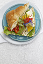 Pita sandwich with bell pepper and feta cheese on plate, elevated view - SCF00408