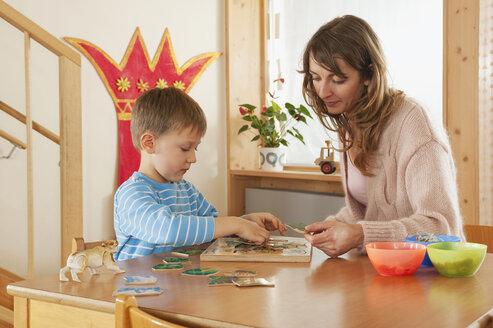Germany, Female nursery teacher and boy (4-5) doing jigsaw puzzle, portrait - RNF00214