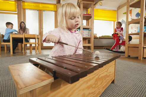 Germany, Girl (3-4) playing xylophone, Female nursery teacher with children in background, portrait - RNF00211
