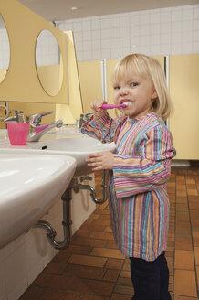 Germany, Girl (3-4) in lavatory  brushing her teeth, side view, portrait - RNF00199