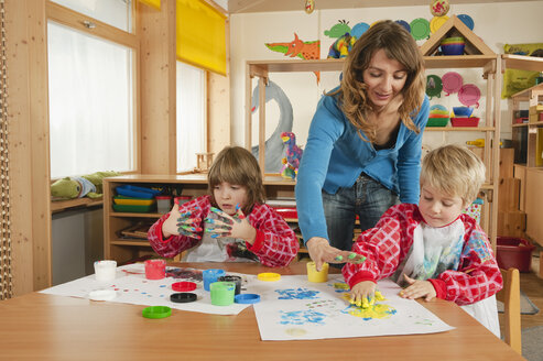 Germany, Two boys (3-4), (6-7) fingerpainting in nursery - RNF00178