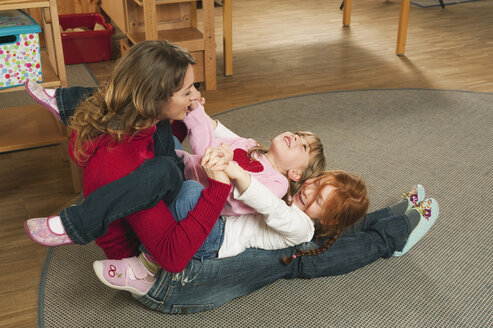 Germany, Nursery, Female nursery teacher and children playing together - RNF00133