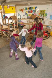 Germany, Nursery, Female nursery teacher and children dancing - RNF00118