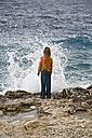 Croatia, Korcula, Girl (8-9) standing by sea looking at splashing wave, rear view - GNF01183