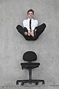 Businessman floating above chair, smiling, portrait, elevated view - BAEF00077