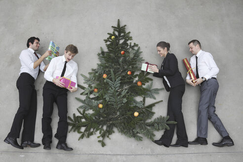 Four business people with Christmas presents standing round Christmas tree, elevated view - BAEF00065