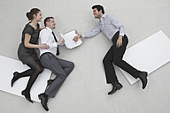 Three business people, businessman signing contract, elevated view - BAEF00053