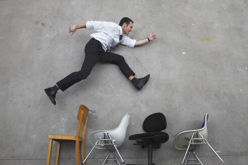 Businessman jumping over chairs, side view, elevated view - BAEF00023