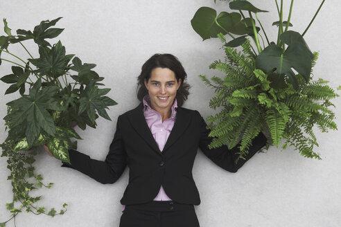 Businesswoman holding Foliage Plants, portrait, elevated view - BAEF00014