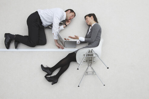 Businessman and businesswoman using laptop, portrait, elevated view - BAEF00002
