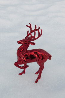 Shiny plastic stag standing in snow, winter. - AWDF00486