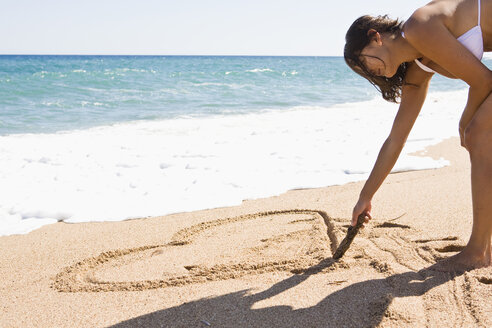France, Corsica, Woman drawing heart shape in sand on beach - SSF00054