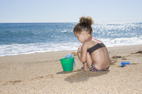 France, Corsica, Girl (2-3) playing with sand on beach - SSF00048
