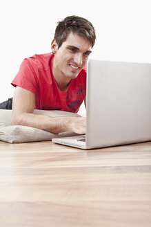Young man lying on floor using laptop, smiling - SSF00042
