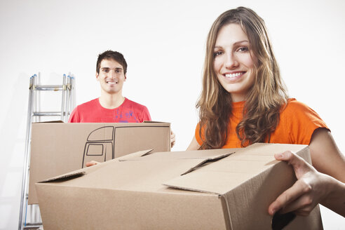 Young couple carrying cardboard boxes, smiling, portrait - SSF00036